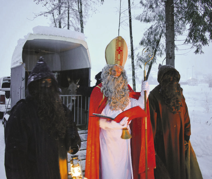 Samichlaus bescherte Kinder  bei Schneefall im Wald